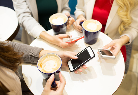 coffee table: drinks, communication, leisure, technology and people concept - close up of hands with coffee cups and smartphones Stock Photo
