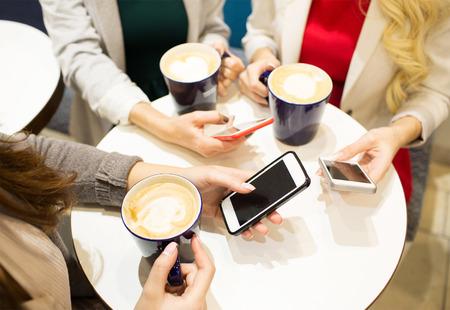 Bevande, comunicazione, tempo libero, tecnologia e concetto di persone - close up di mani con tazze di caffè e smartphone