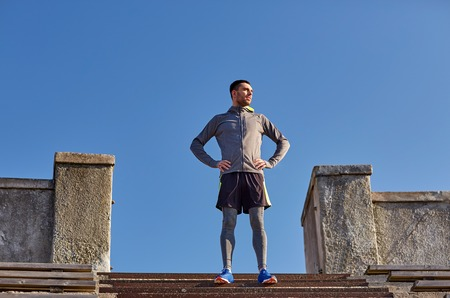 hombre flaco: fitness, deporte, la gente y el concepto de estilo de vida - hombre feliz en la escalera estadio Foto de archivo