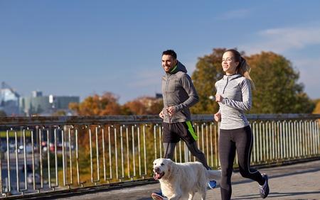 perro corriendo: fitness, deporte, la gente y el estilo de vida concepto - feliz pareja con perro corriendo al aire libre