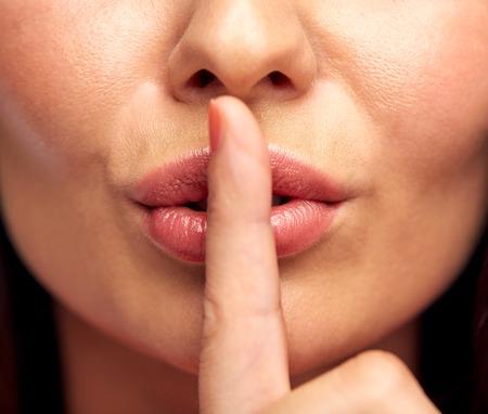 Le silence, le geste et la beauté notion - Gros plan d'une jeune femme tenant un doigt sur les lèvres Banque d'images - 50944430