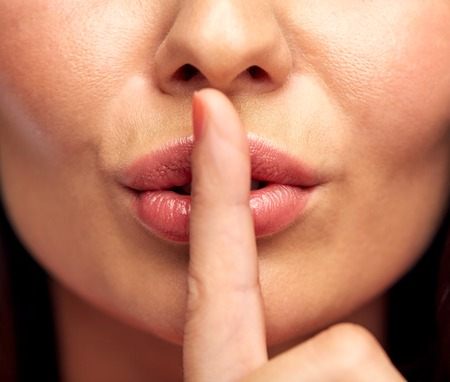 quiet: silence, gesture and beauty concept - close up of young woman holding finger on lips