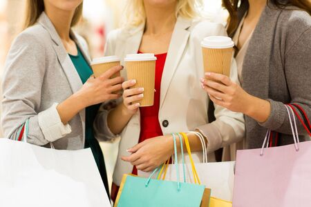 consumerism: sale, drinks, consumerism and people concept - close up of women with shopping bags and coffee cups