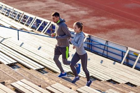 フィットネス、スポーツ、運動、ライフ スタイル コンセプト - スタジアムの 2 階を実行するカップル