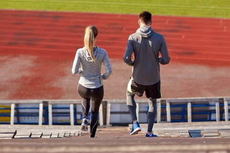 downstairs: fitness, sport, exercising and lifestyle concept - couple walking downstairs on stadium Stock Photo
