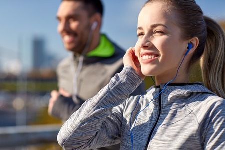 podcast: fitness, sport, people, technology and lifestyle concept - happy couple running and listening to music in earphones at city