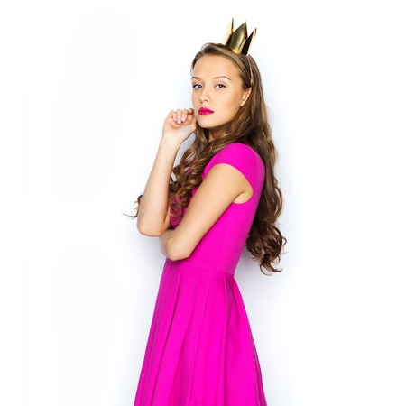 supercilious: people, holidays and fashion concept - young woman or teen girl in pink dress and princess crown Stock Photo