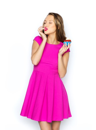 cupcakes: people, holidays, party, junk food and celebration concept - happy young woman in pink dress eating birthday cupcake Stock Photo