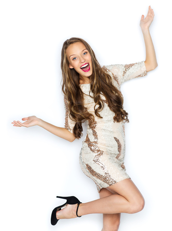 people, style, holidays, hairstyle and fashion concept - happy young woman or teen girl in fancy dress with sequins and long wavy hair having fun