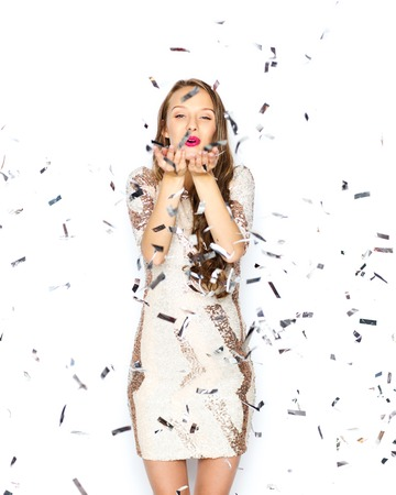 people, holidays, gesture and glamour concept - happy young woman or teen girl in fancy dress with sequins and confetti at party sending blow kiss Фото со стока
