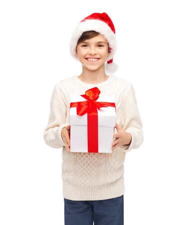 happy christmas: holidays, presents, christmas, childhood and people concept - smiling happy boy in santa hat with gift box Stock Photo