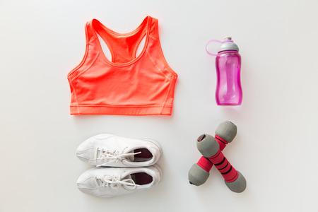 estilo de vida: desporto, fitness, estilo de vida saudável e objetos conceito - close up da fêmea vestuário desportivo, halteres e conjunto de garrafa