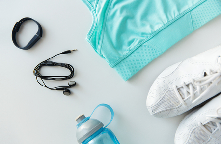 sport fitness: sport, fitness, healthy lifestyle and objects concept - close up of female sports clothing, heart-rate watch, earphones and bottle set