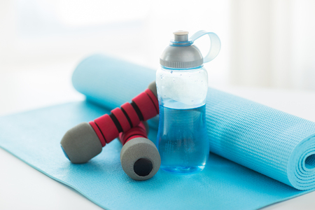 mat: sport, fitness, healthy lifestyle and objects concept - close up of bottle with water, dumbbells and sports mat