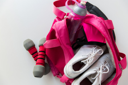 gym shoes: sport, fitness, healthy lifestyle and objects concept - close up of female sports stuff in backpack and dumbbells