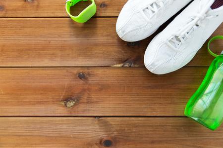 sport, fitness, gezonde leefstijl en objecten concept - close-up van sportschoenen, armband en een fles water op een houten vloer