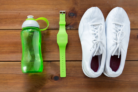 sport object: sport, fitness, healthy lifestyle and objects concept - close up of sneakers, bracelet and water bottle on wooden floor