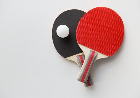 Sport, Fitness, gesunde Lebensweise und Konzept-Objekte - Nahaufnahme von Tischtennisschlägern mit Ball Standard-Bild