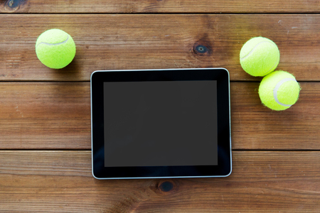 three objects: sport, technology, game and objects concept - close up of three yellow tennis balls and tablet pc computer on wooden floor Stock Photo