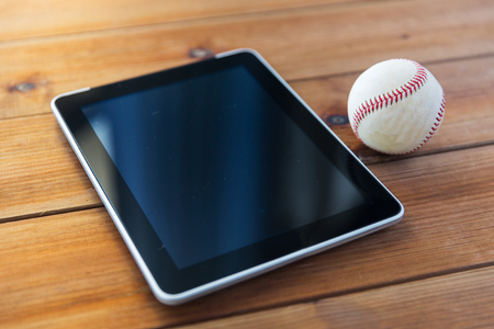 baseball stuff: sport, technology, game and objects concept - close up of baseball ball and tablet pc computer on wooden floor