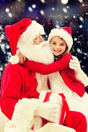 snow man party: holidays, christmas, childhood and people concept - smiling little girl hugging with santa claus over snowy city background