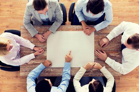 gente sentada: negocios, personas y concepto de trabajo en equipo - primer plano de equipo creativo sentado en la mesa y que señala el dedo en el papel en blanco en la oficina Foto de archivo