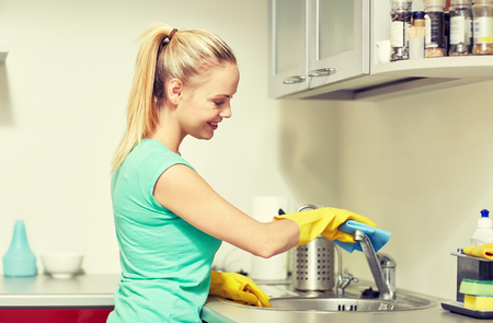 sink: people, housework and housekeeping concept - happy woman in protective gloves cleaning tap with rag at home kitchen