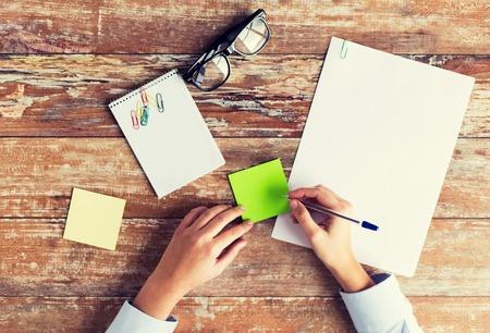 affaires, l'éducation et les gens concept - gros plan des mains des femmes avec des papiers, des autocollants et des lunettes sur la table