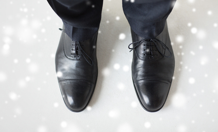 view an elegant wardrobe: people, business, fashion and footwear concept - close up of man legs in elegant shoes with laces or lace boots over snow effect Stock Photo