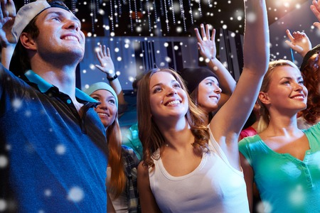 out time: party, holidays, celebration, nightlife and people concept - smiling friends waving hands at concert in club and snow effect
