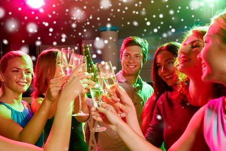 partido del año nuevo, días de fiesta, celebración, vida nocturna y la gente concepto - amigos sonriendo tintineo copas de champán sin alcohol en el club y la nieve efecto