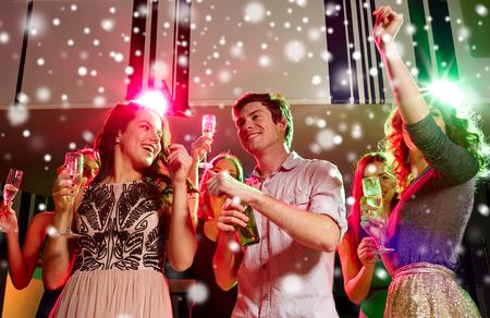 sektglas: Party des neuen Jahres, Ferien, feiern, das Nachtleben und die Menschen Konzept - lächelnde Freunde stossen mit alkoholfreien Sekt und Bier im Club und Schnee-Effekt