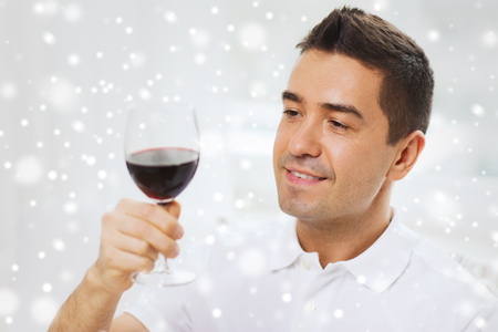 degustating: profession, drinks, leisure, holidays and people concept - happy man drinking red wine from glass over snow effect