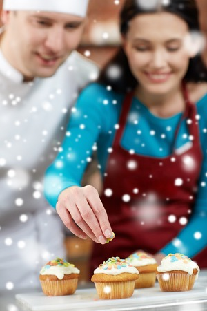 courses: cooking class, culinary, bakery, food and people concept - happy group of woman and male chef cook baking in kitchen over snow effect