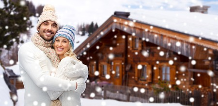 winter vacation: winter, vacation, couple, christmas and people concept - smiling man and woman in hats and scarf hugging over wooden country house and snow background Stock Photo