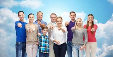 family and friends: family, gender, generation and gesture concept - group of happy people pointing finger on you over blue sky and clouds background