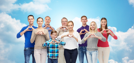 gesture, family, generation and people concept - group of smiling men, women and boy showing heart shape hand sign over blue sky and clouds background Stockfoto