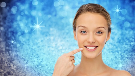 beauty, people and health concept - happy young woman pointing finger to her smile or teeth over blue holidays lights or glitter background