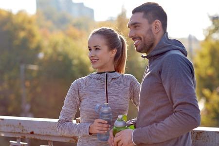 parejas felices: fitness, deporte, la gente y el estilo de vida concepto - sonriente pareja con botellas de agua al aire libre