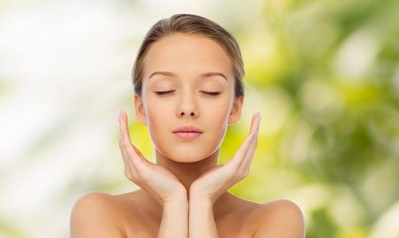 schoonheid, mensen, huidverzorging en gezondheid concept - jonge vrouw gezicht en handen over groene natuurlijke achtergrond Stockfoto