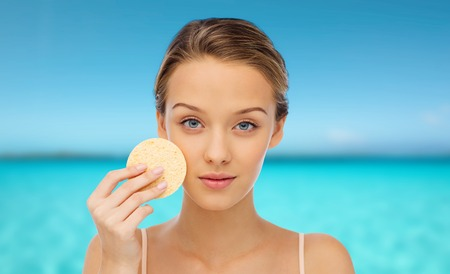 exfoliate: beauty, people, hygiene, and skincare concept - young woman cleaning face with exfoliating sponge over blue sea and sky background