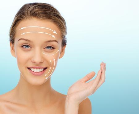 kunststoff: Schönheit, Heben, plastische Chirurgie, Anti-Aging und Menschen Konzept - lächelnde junge Frau auf blauem Hintergrund mit weißen Pfeilen auf Gesicht