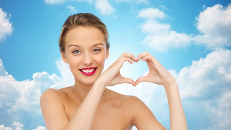heart in hand: beauty, people, love, valentines day and make up concept - smiling young woman with pink lipstick on lips showing heart shape hand sign over blue sky and clouds background