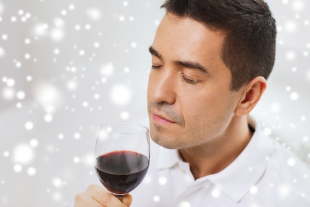 degustating: profession, drinks, leisure and people concept - happy man drinking and smelling red wine from glass over snow effect