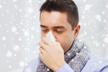 flu virus: healthcare, flu, people, rhinitis and medicine concept - close up of ill man blowing his nose with paper napkin at home over snow effect Stock Photo