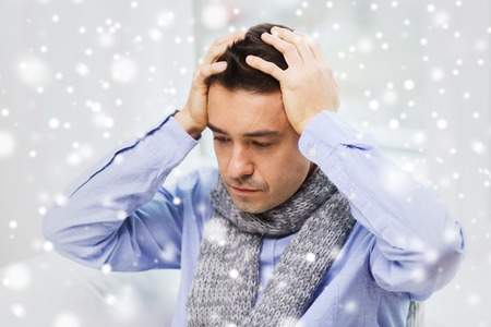 grippe: health care, people, winter and medicine concept - close up of ill man with flu suffering from headache at home over snow effect Stock Photo