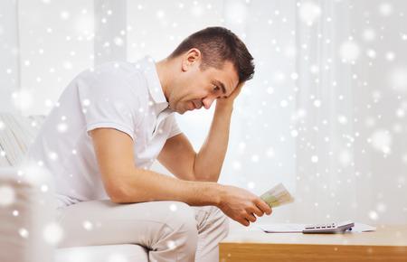 persona triste: negocio, el ahorro, la crisis financiera y la gente concepto - hombre con dinero y calculadora en el país más de efecto de nieve