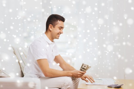business savings: business, savings, finances, income and people concept - happy man with papers and calculator counting dollar money at home over snow effect