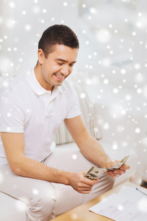 business savings: business, savings, finances, income and people concept - man with papers counting money at home over snow effect