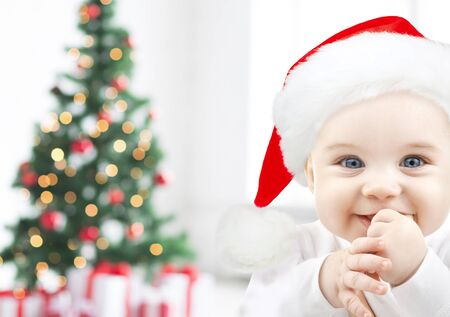 babyhood: holidays, babyhood, childhood and people concept - happy baby in santa hat over christmas tree lights and gifts background Stock Photo